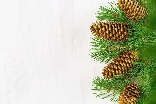 松の枝と天然金の円錐形からのクリスマスの装飾。コピースペース。