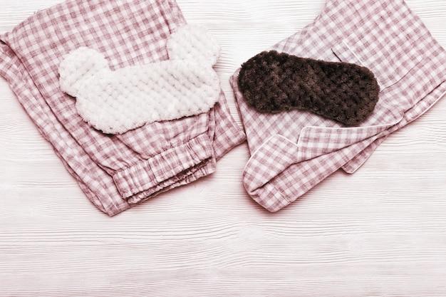 寝ている服、暖かいソフトパジャマ、コピースペースを持つ白い木製の背景にふわふわのマスク。