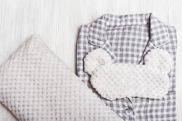 グレーのパジャマ、ふわふわの睡眠マスク、柔らかい枕。
