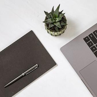 ラップトップコンピューター、ペン、小さなサボテンポットと白い最小限のオフィスデスクテーブル。コピースペースを持つトップビュー。平干し。