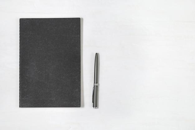 白い机の背景に光沢のあるペンで閉じた黒いカバーノートの平面図です。コピーブックをモックアップします。文房具付きの最小限のオフィスデスク。