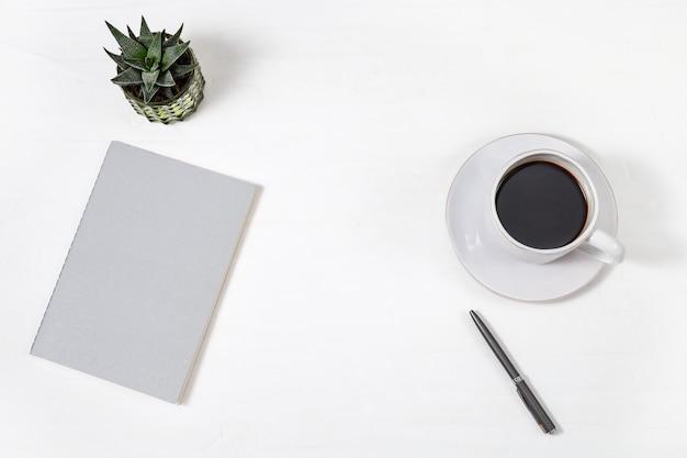 閉じたコピーブック、コーヒーの白いカップ、ペン、緑の多肉植物と白い作業テーブルの平面図。学校やオフィスの作業スペース。コピースペース。平干し。