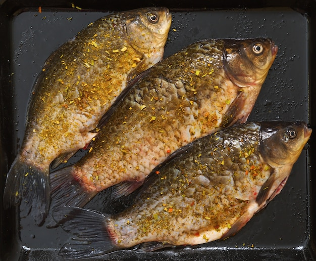 Свежая рыба карась с пряностями.