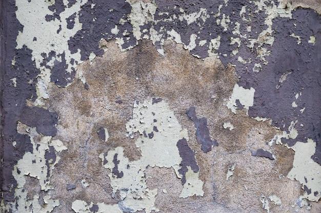 建物の古い壁は、ひび割れで覆われ、剥離する塗料で、年齢とともに崩れています。古いセメント表面の背景。