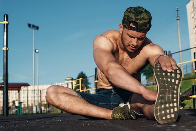 若い男がスポーツのフィールド、アスリートに伸びる
