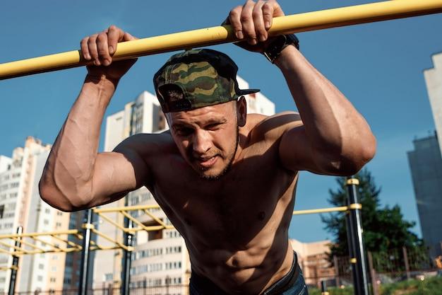 Молодой человек делает упражнения на брусьях на стадионе, спортсмен