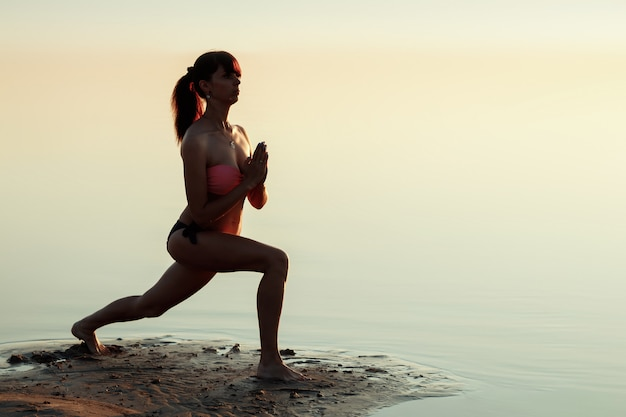 若い女の子のシルエット、自然にヨガ、湖と美しい夕日の
