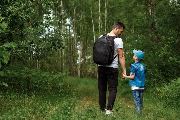 バックパックを持った男、父親と息子がハイキングに出て、森の中を散歩している間。