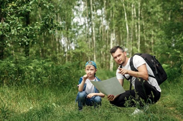 バックパックを持った男、父親と息子がハイキングに出かけ、地図を見て、森の中を歩きながら歩きます。