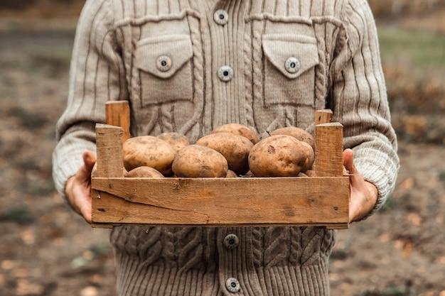 庭でジャガイモの収穫を手で保持している農家。