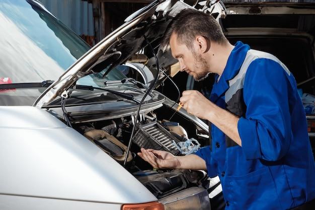 男性の手のクローズアップ、エンジンのオイルレベルをチェックします。