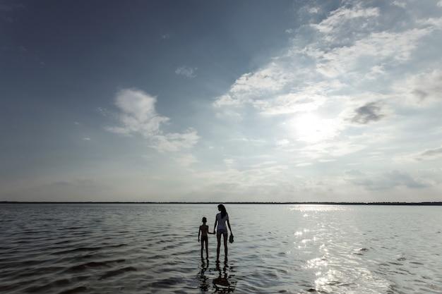Мама и ребенок стоят в воде против красивый закат на озере.