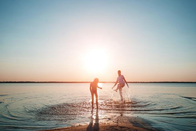 Семья на озере против красивого захода солнца.
