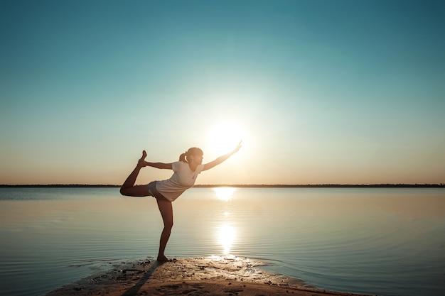 湖と美しい夕日の少女シルエット