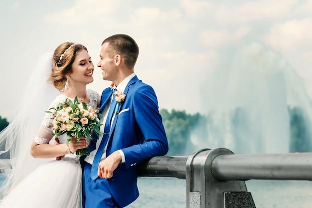 美しい男と女、白いウェディングドレスの花嫁、自然を背景に古典的な青いスーツの新郎。結婚式、家族の創造。
