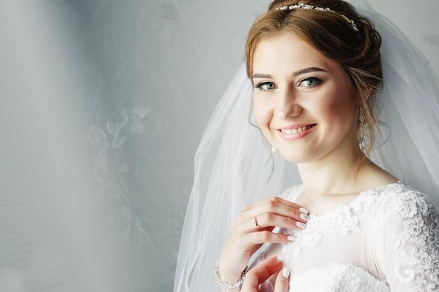 Красивая девушка, невеста в белом платье на фоне квартиры. свадьба, сбор невесты, создание семьи.
