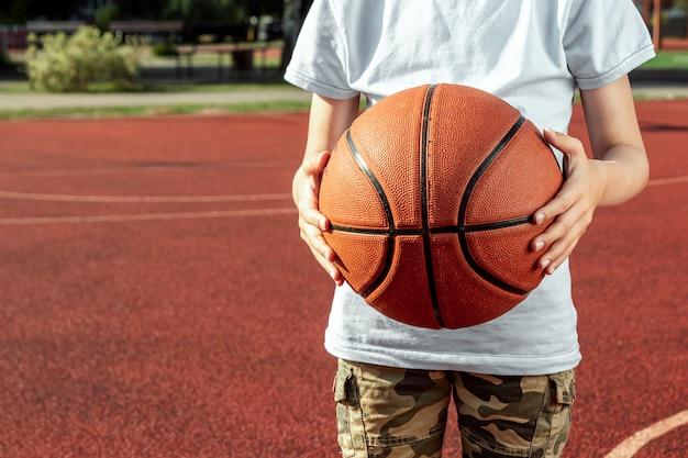 少年は彼の手でバスケットボールのクローズアップを保持します