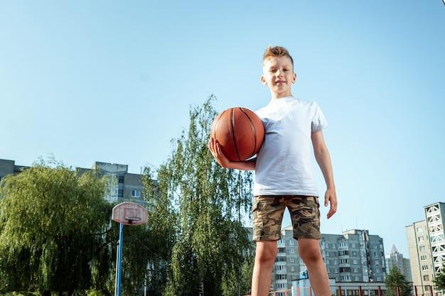 Портрет мальчика с баскетболом на баскетбольной площадке