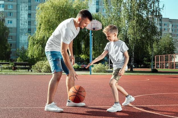 父と息子が一緒にバスケットボールコートでバスケットボールをする