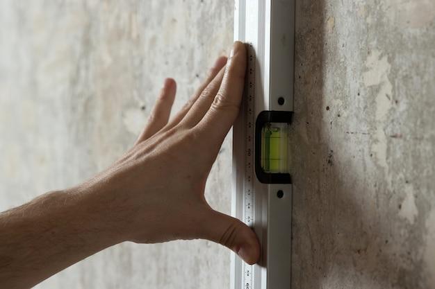 男は定規で壁を測定します