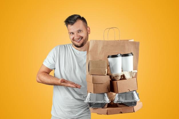 Человек в яркой футболке дает заказ быстрого питания, изолированных на желтом фоне