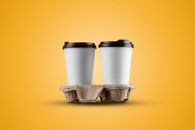 黄色の背景に分離された紙の白いコーヒーカップ