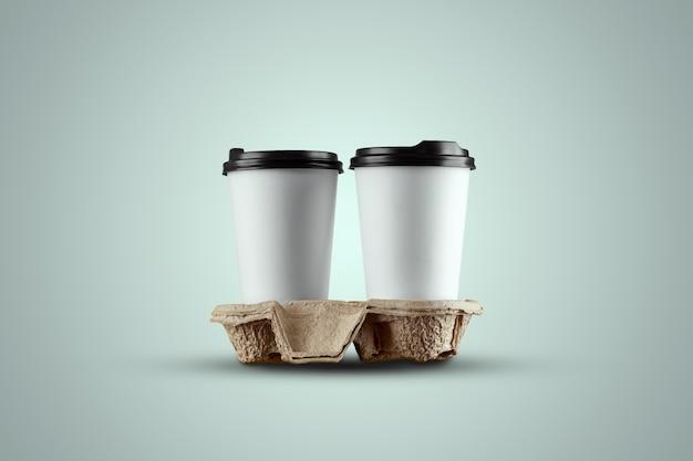 青色の背景に分離された紙の白いコーヒーカップ