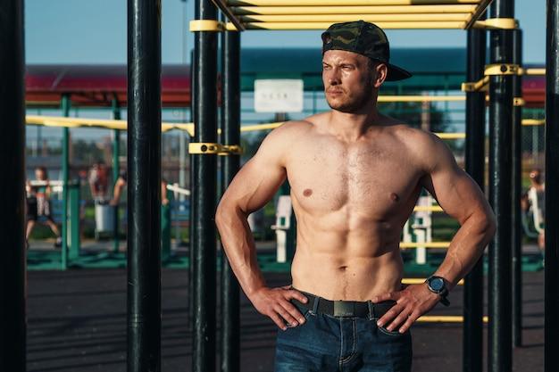 トレーニング、アスリート、市内の屋外トレーニングの後休んでいる裸の胴体を持つ若い筋肉男