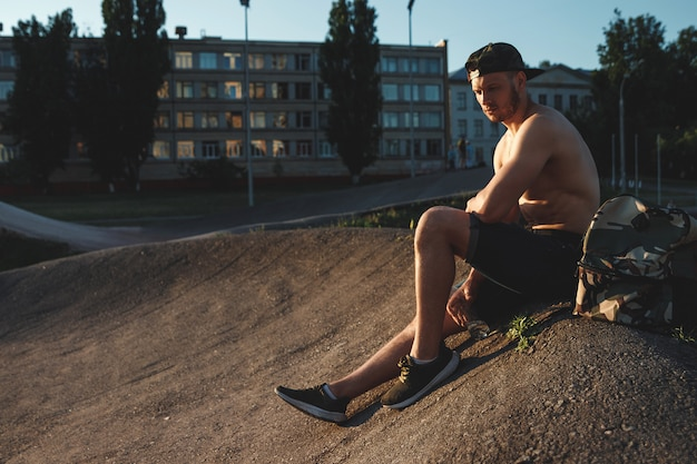 トレーニング、スポーツマン、市内の屋外トレーニングの後休んで若い男