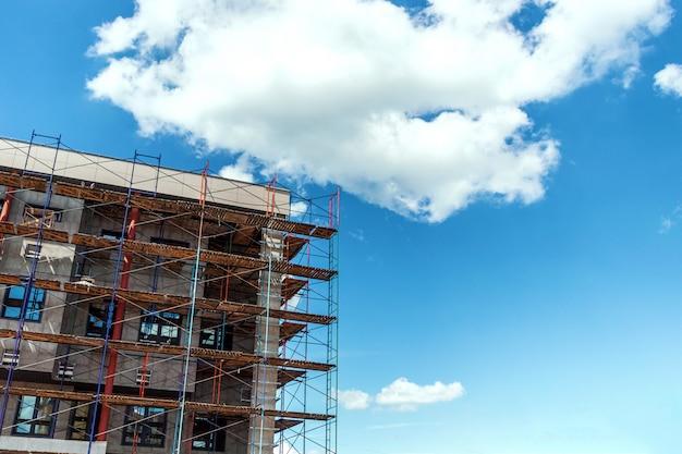 Строительные леса, предоставляя площадки для незавершенного строительства нового жилого здания