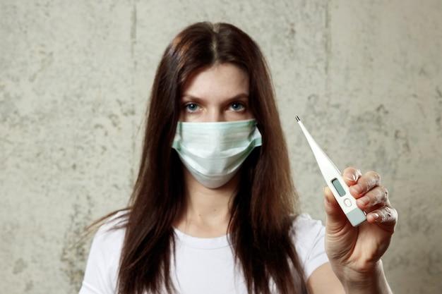 温度計を保持していると医療用マスクを身に着けている若い、美しい、病気の少女の肖像画