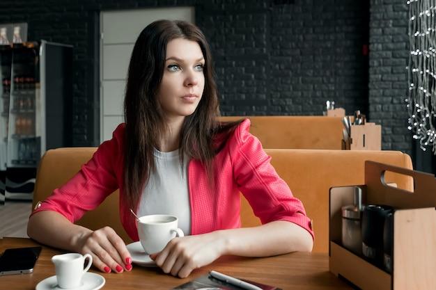 肖像画、若い女の子は一杯のコーヒーのためにカフェで時間を費やしています。ビジネスランチ。