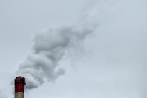 煙が灰色の空を背景に流れるパイプ