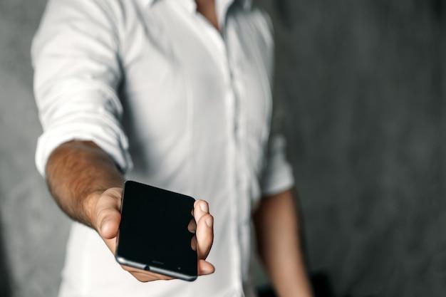 クローズアップ、携帯電話を持つ男の手の上にコンクリート。実業家。