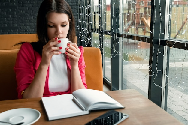Молодая красивая девушка, предприниматель, пить чай или кофе, сидя в кафе