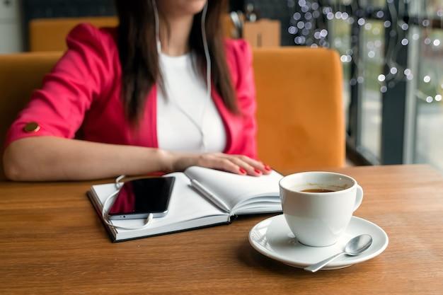 カフェに座って音楽を聴くヘッドフォンの女の子。休憩、ビジネスランチ、日記。