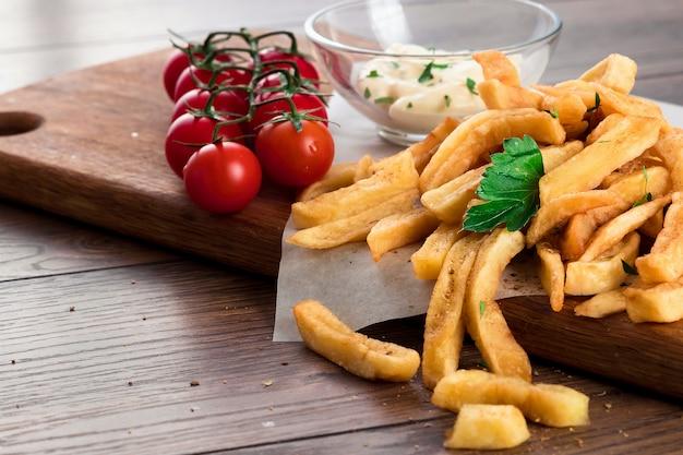 フライドポテト、チェリートマト、木のガーリックソース