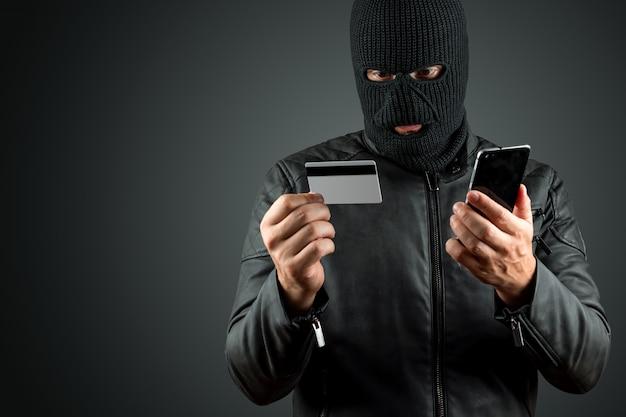 目出し帽の強盗は、暗い背景に彼の手でクレジットカードを保持しています。
