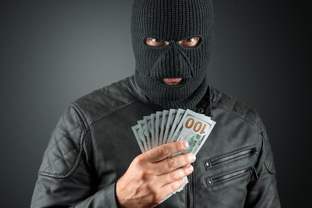 Грабитель в балаклаве держит в руках доллары на темном фоне