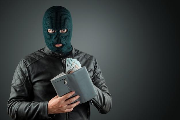 目出し帽の泥棒は、暗い背景に彼の手でドルを保持しています