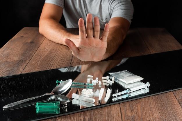 停止ジェスチャーを持つ男は、薬物を拒否します。薬物中毒との戦い。