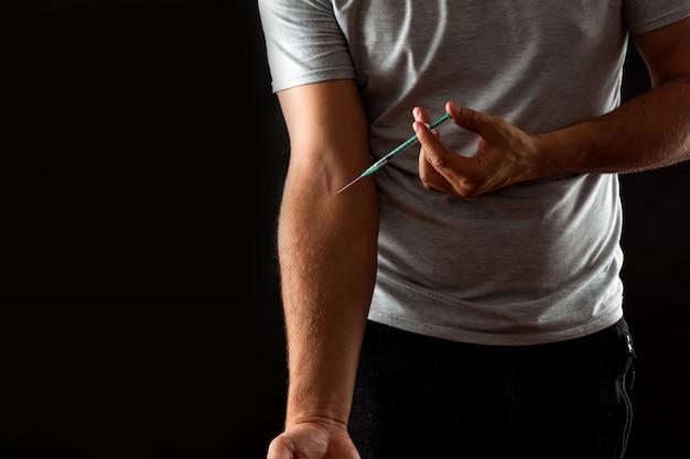 Мужчина вводит шприц в вену