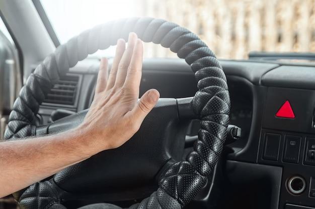 男性の手が車のステアリングホイールの信号を押す