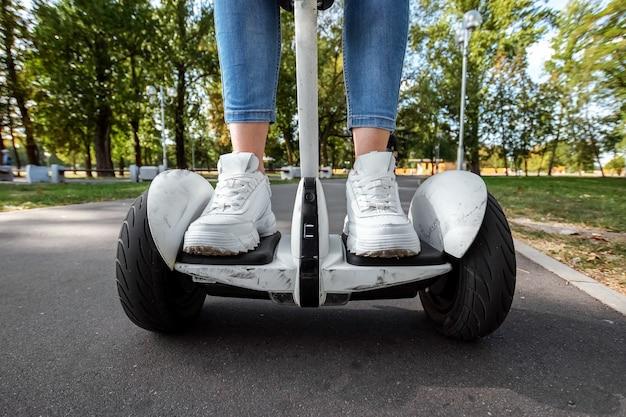 公園のクローズアップで白いホバーボード上の白いスニーカーの女の子の足