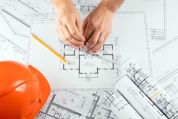 男性の手、オレンジ色のヘルメット、鉛筆、建築工事図面、巻尺。