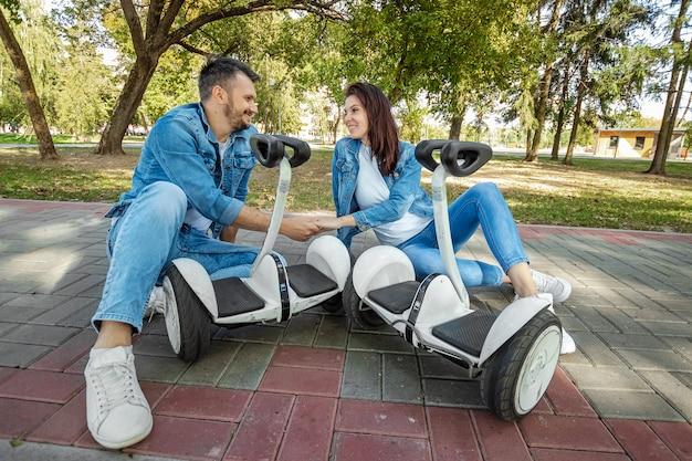公園でホバーボードに乗る若いカップル