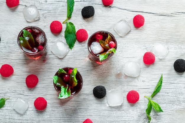 Красные бокалы застрелили алкогольный холодный коктейль с клюквой, малиной и мятой