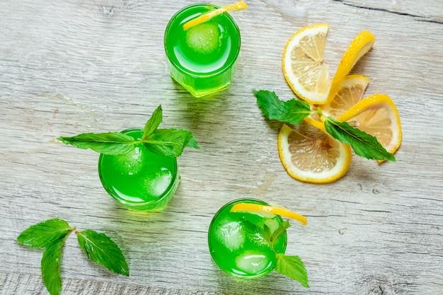 Зеленые бокалы застрелили алкогольный холодный коктейль с клюквой, малиной, лимоном и мятой