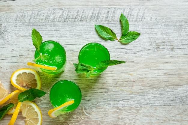 緑の脚付きグラスショットクランベリーラズベリーレモンとミントとアルコールの冷たいカクテル