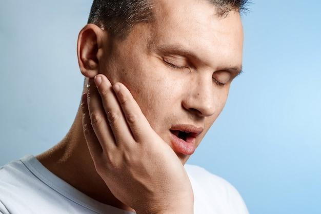 歯痛。青の男のクローズアップの肖像画